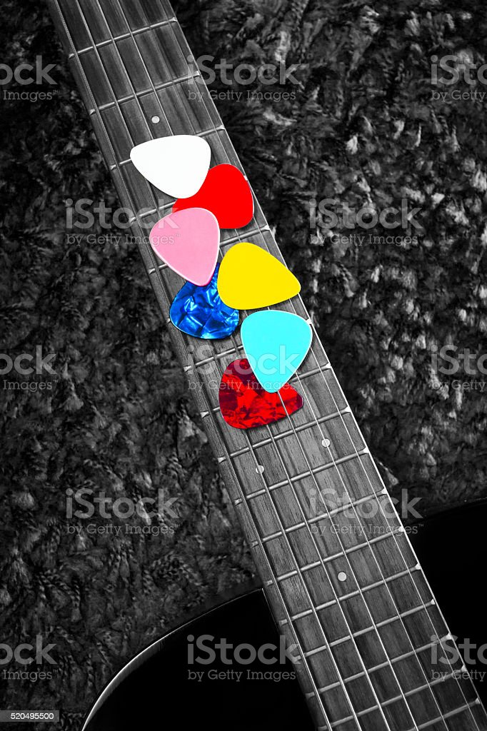 colourful picks on acoustic guitar fingerboard stock photo