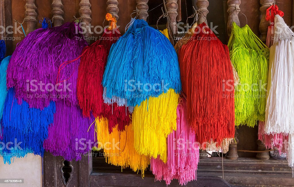 Colourful rope bunches hanging on the door for sales stock photo