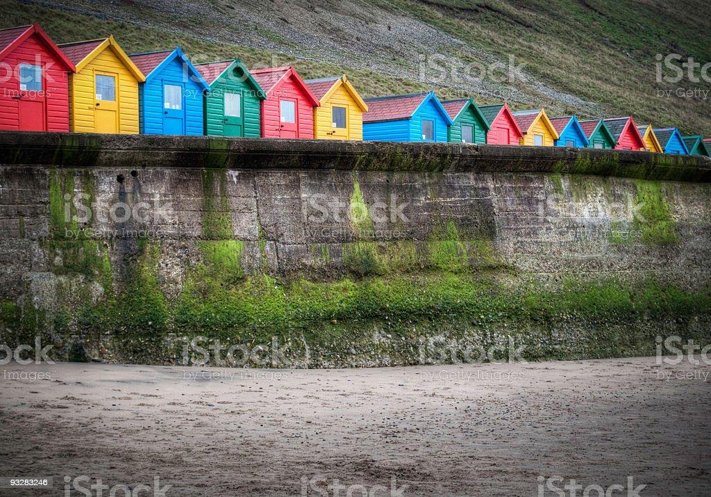 Colourful row of beach huts behind a sea wall royalty-free stock photo