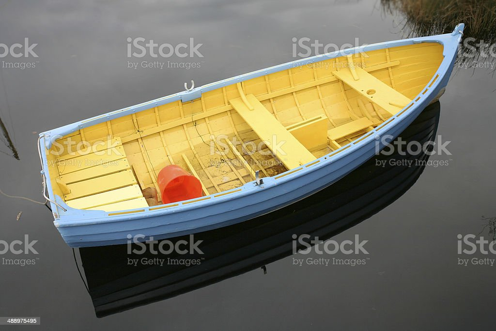 Colourful Rowboat floating on water stock photo