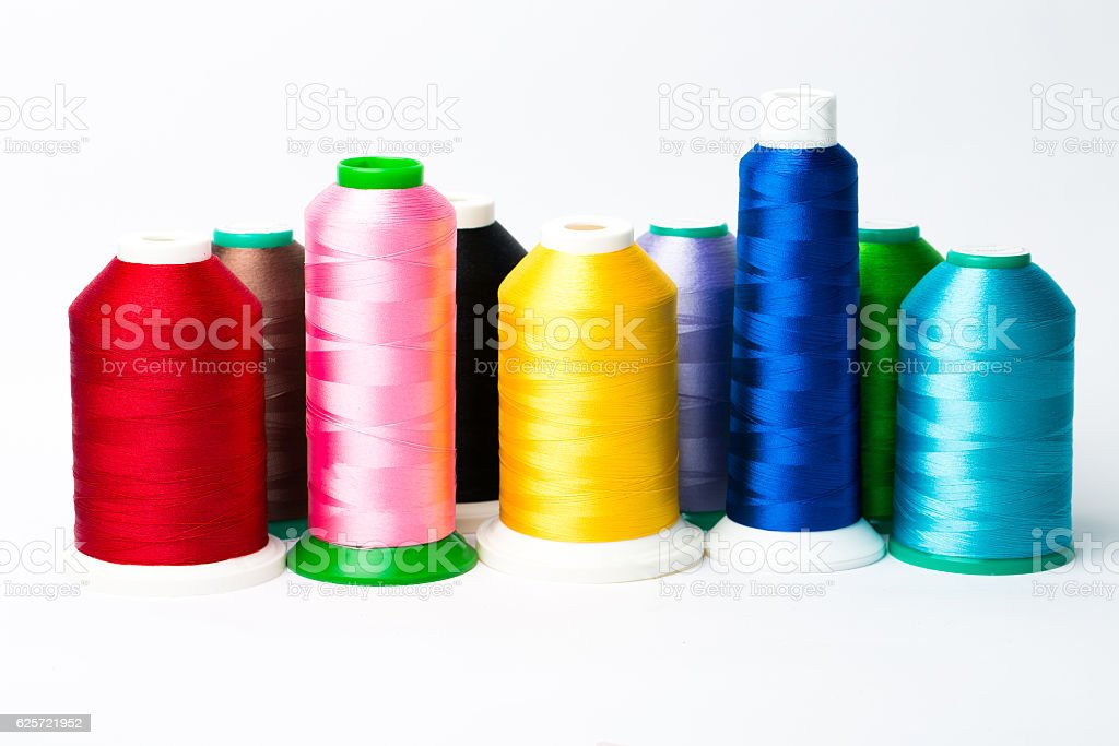 Colourful spools of thread on white background stock photo