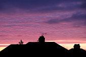 Colourful sunset above house skyline.