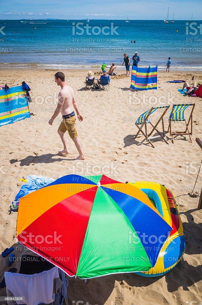 Colourful sunshade on busy beach beside deckchairs and sunbathers England stock photo