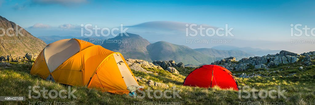 Colourful mountain tents pitched on an idyllic wild camp site high in...