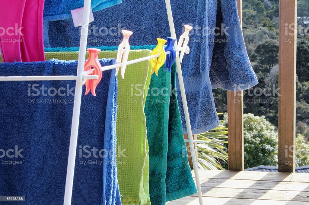 Colourful towels drying on an airer stock photo