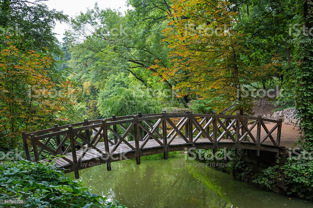 Colourful trees and old wooden bridge in Sofiyivsky park - stock photo