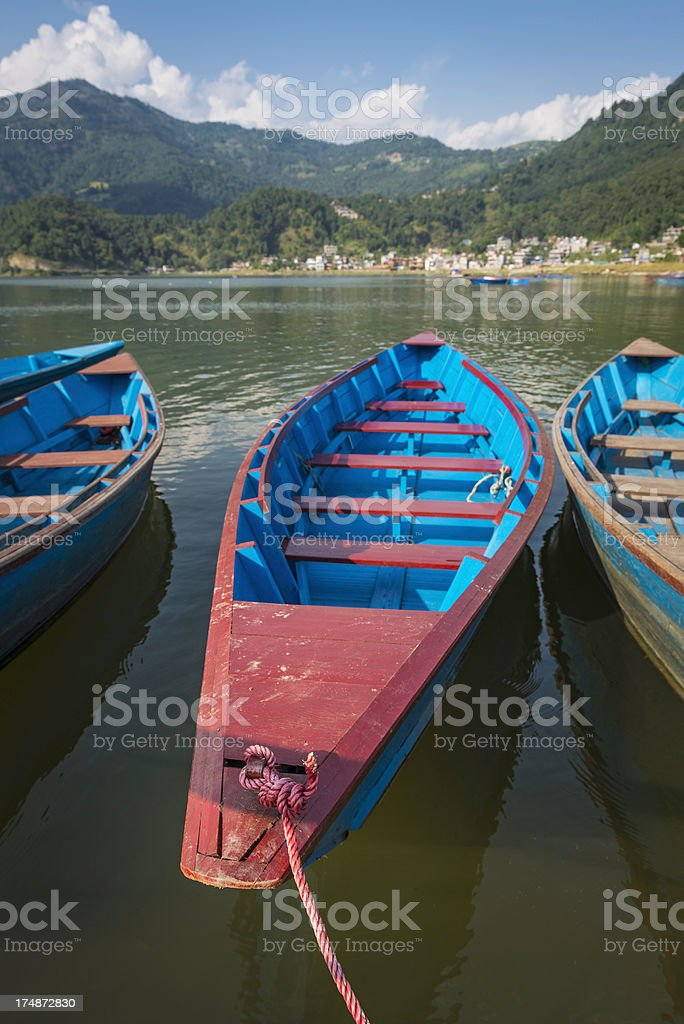 Colourful wooden rowing boats on mountain lake resort stock photo