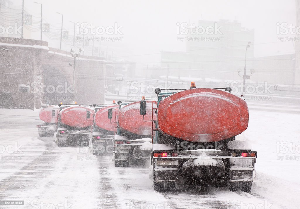 Column of five snow-remover trucks on the road in Moscow royalty-free stock photo