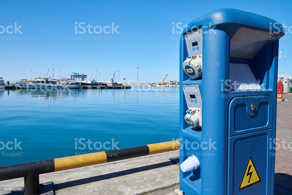 Column with electrical power for yachts and boats on docks stock photo