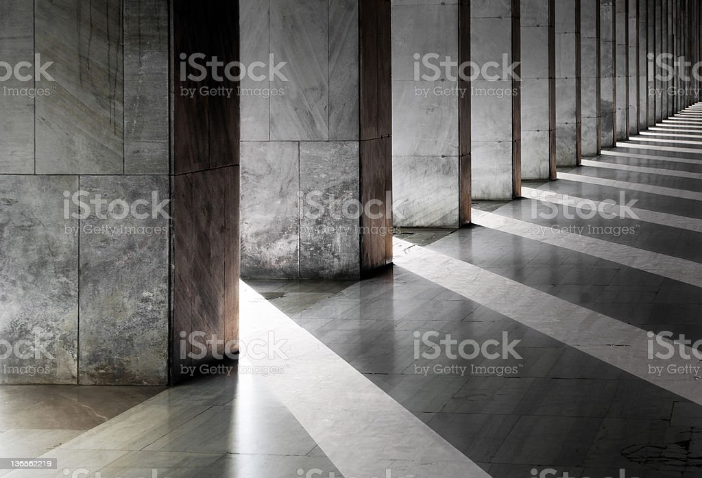 Columns and shadows over an empty hallway stock photo