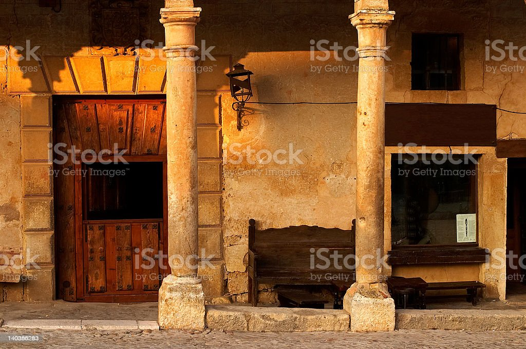 Columns, door and bench in old spanish village at sunset royalty-free stock photo