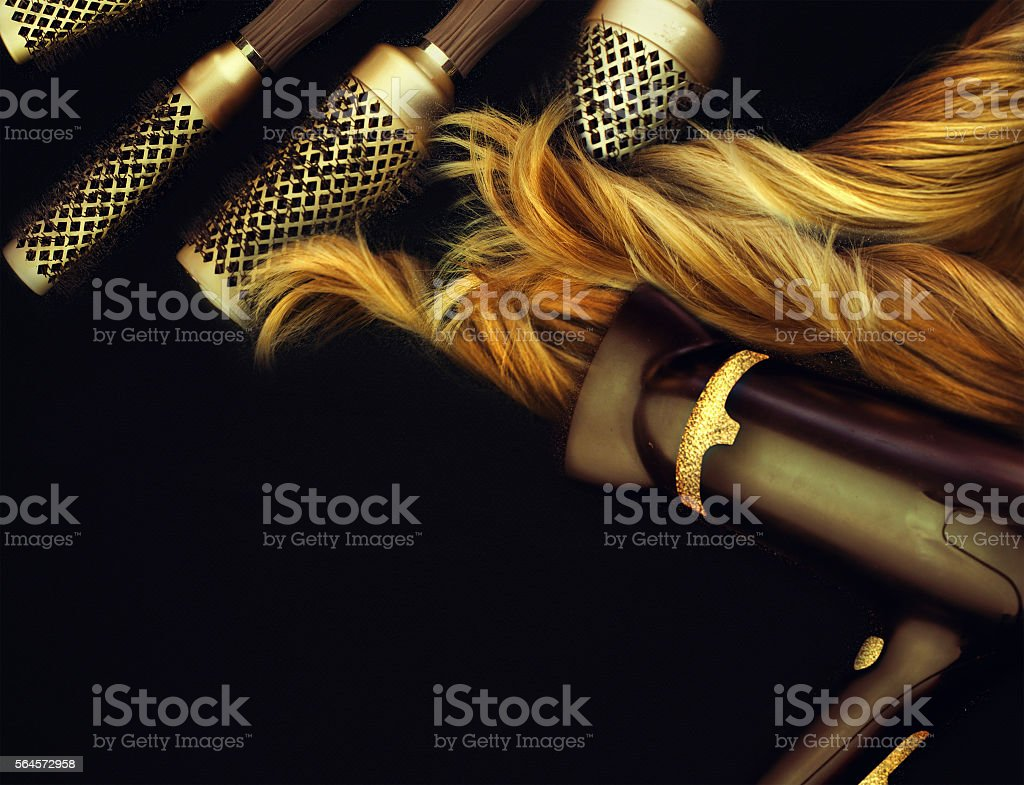 Comb brushes and hairdryer with blond hair. stock photo