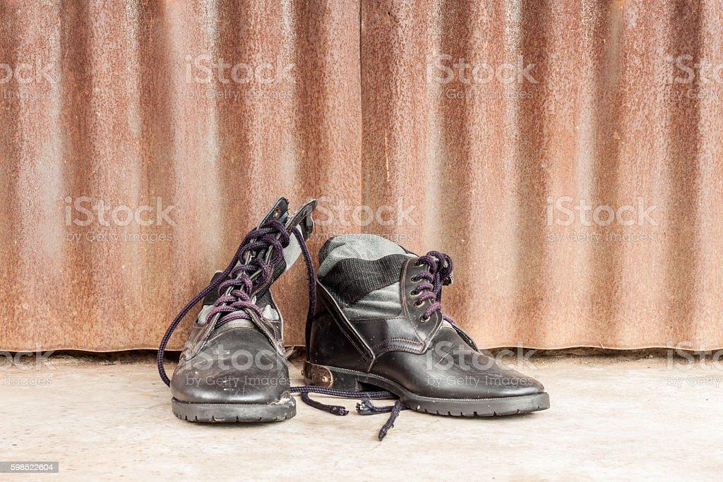 combat boots on cement floor, zinc wall stock photo
