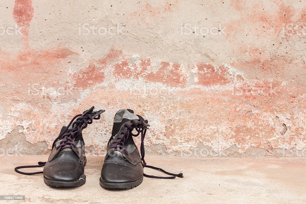 combat boots on cement wall stock photo