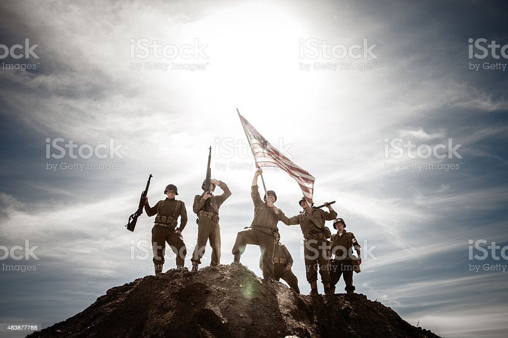 WWII Combat Infantry Squad Waves Flag on Hill stock photo