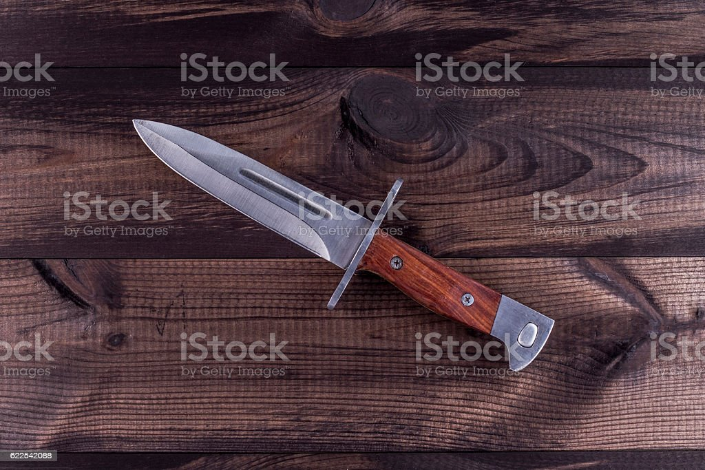 Combat knife on wooden table stock photo