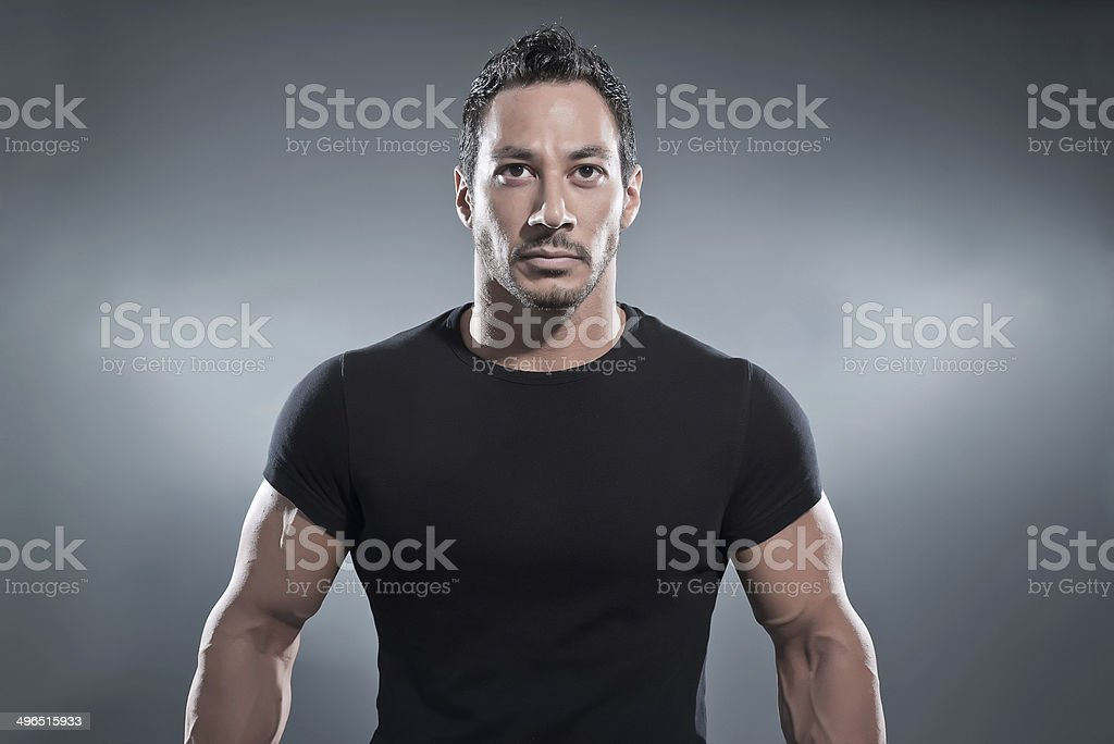 Combat muscled fitness man wearing black shirt and pants. stock photo