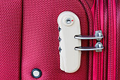 combination lock on red suitcase travel bag