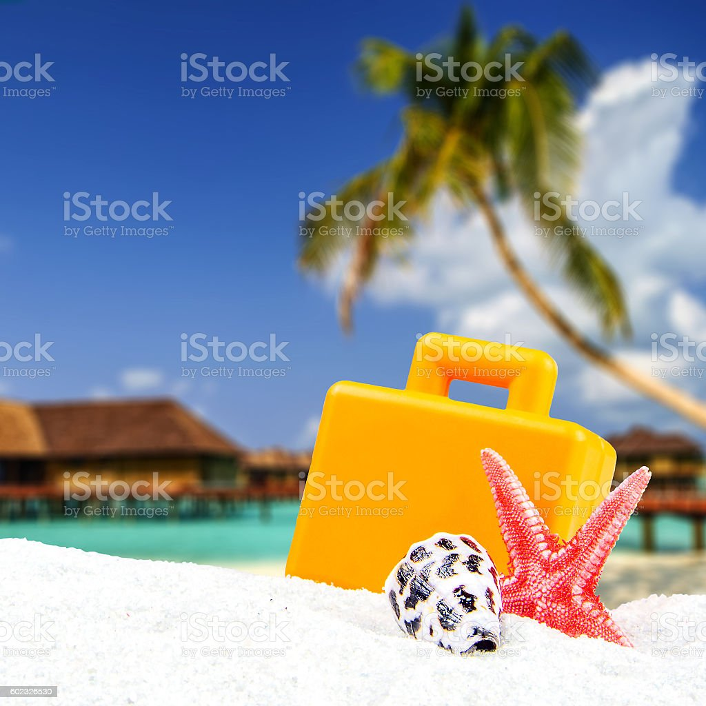 combination of sandy and suitcase front with blurred tropical island stock photo