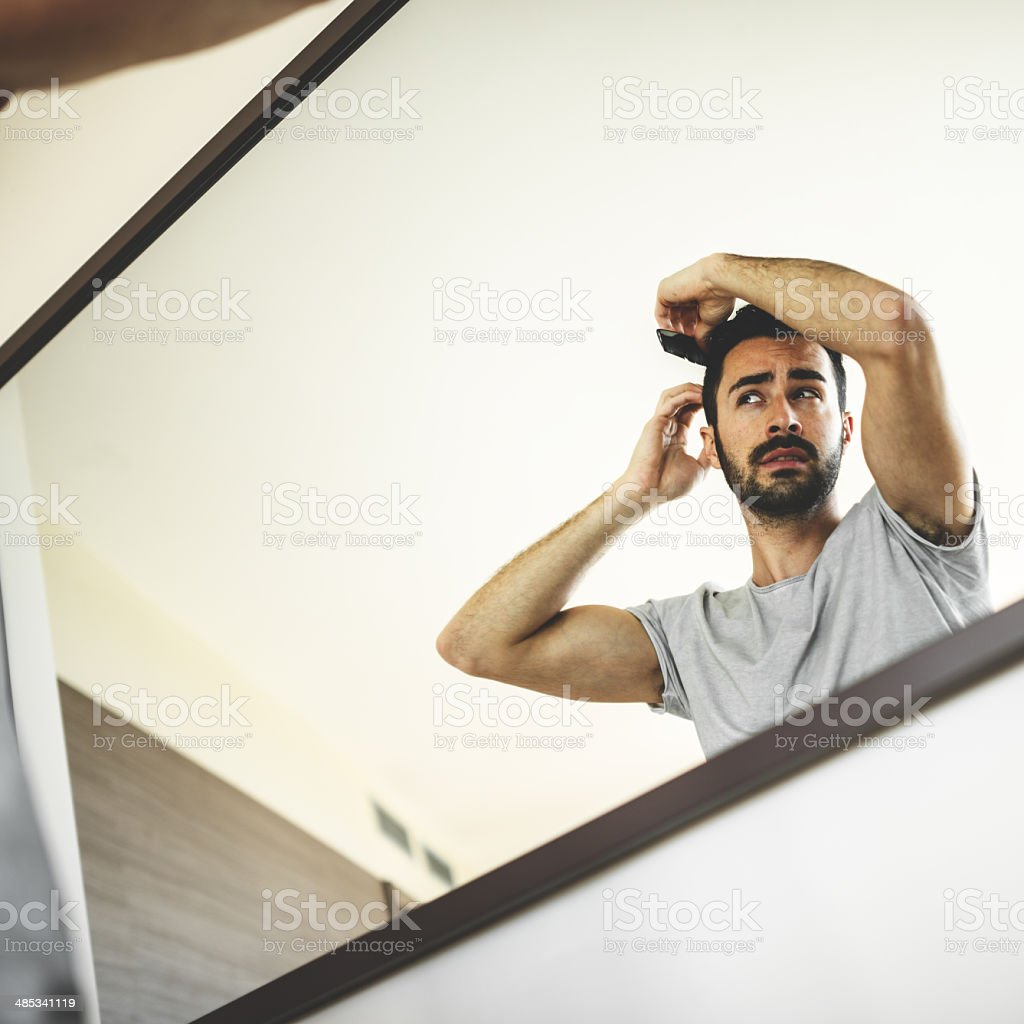 combing the hair in front of mirror stock photo