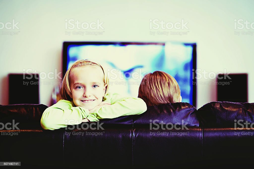 Come watch TV with me! Smiling little girl at home stock photo