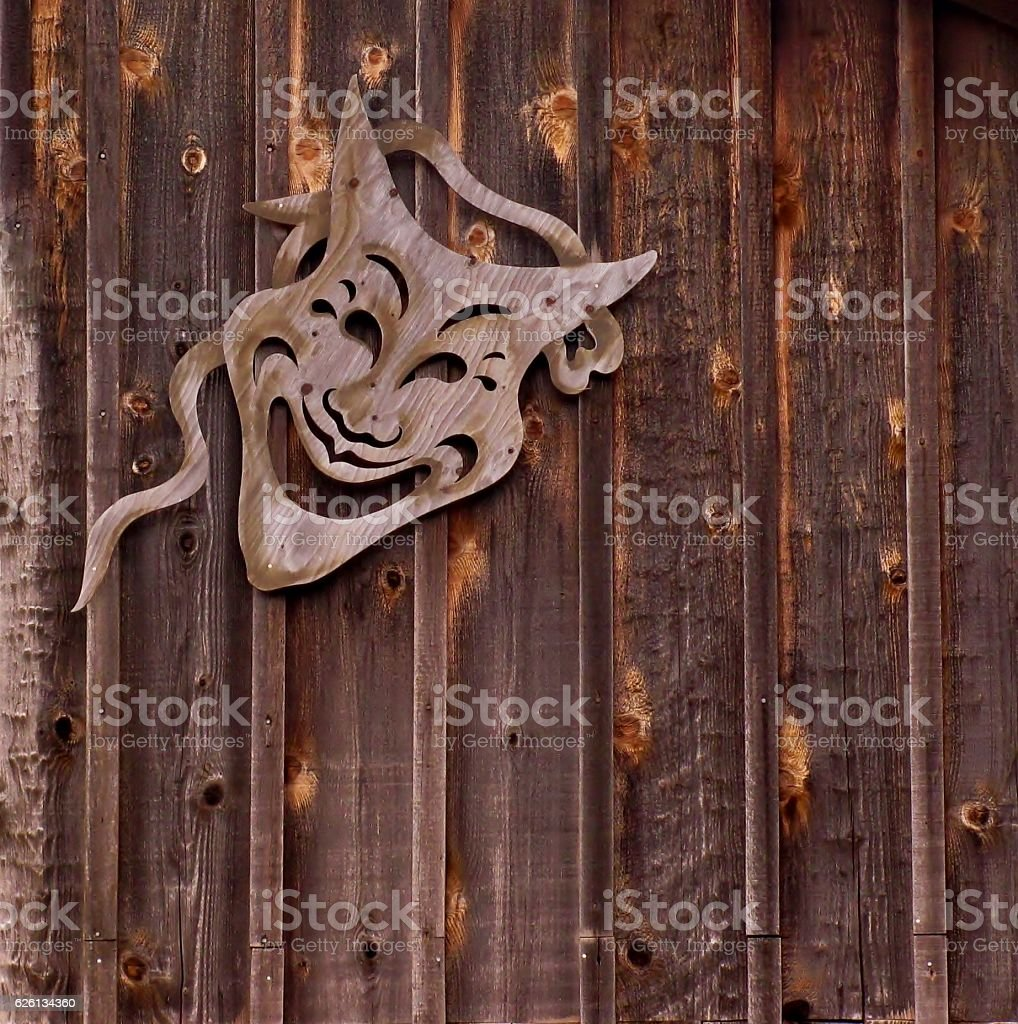 Comedy theatrical mask on wooden background stock photo