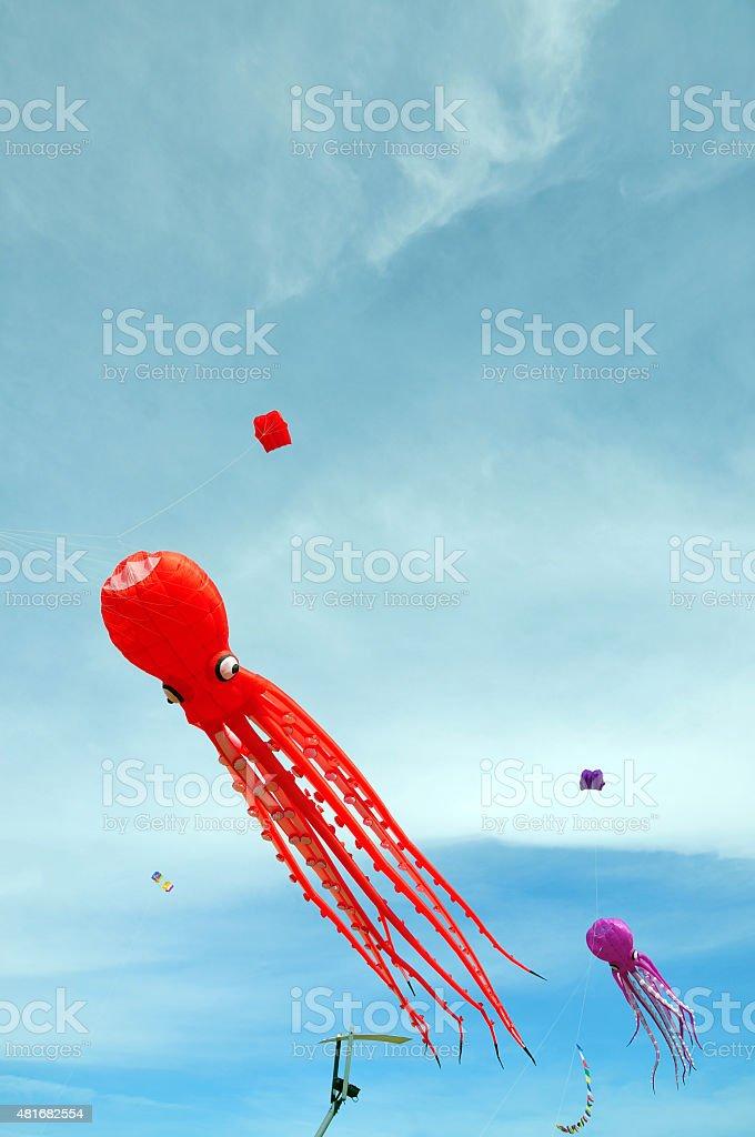 Cometas de colores en una tarde de cielo azul stock photo
