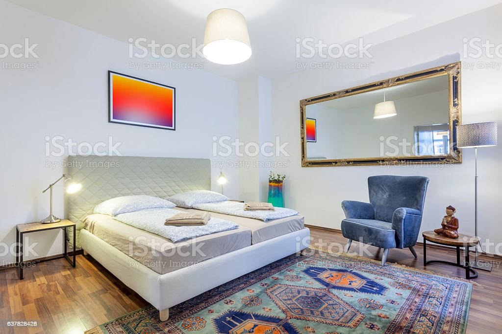 Comfortable and Modern Bedroom with King Bed and Armchair stock photo