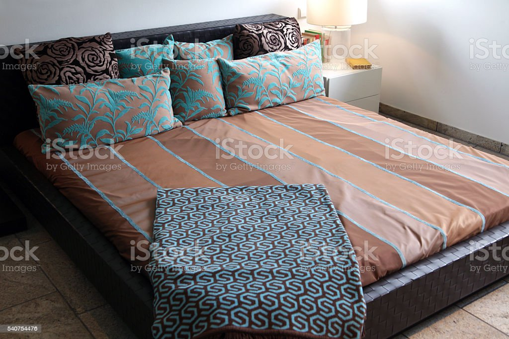 Comfortable bed with brown and turquoise bedware stock photo