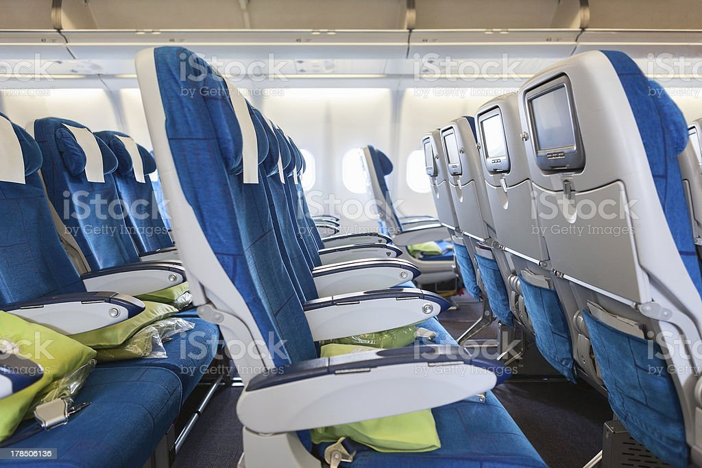 Comfortable seats in jet with screens at chairs back royalty-free stock photo