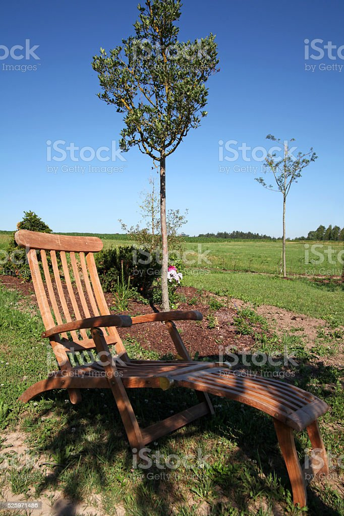 Comfortable wooden lounger in the garden stock photo