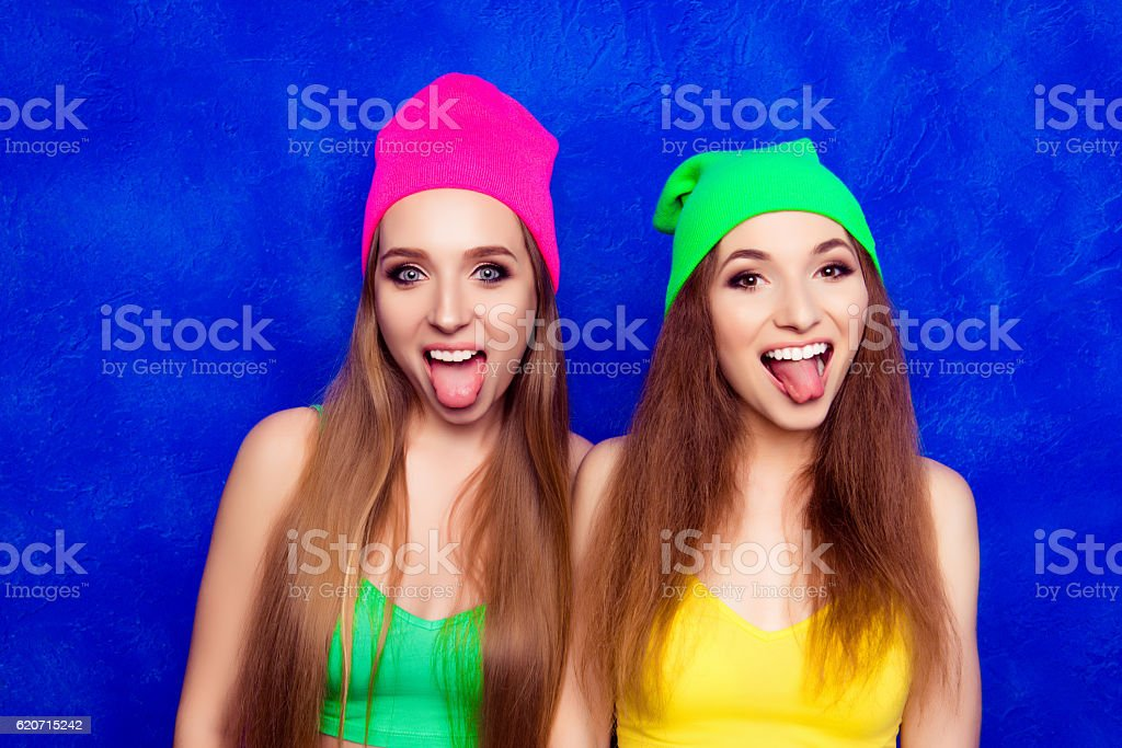 Comic portrait of happy young women in hats showing tongues stock photo