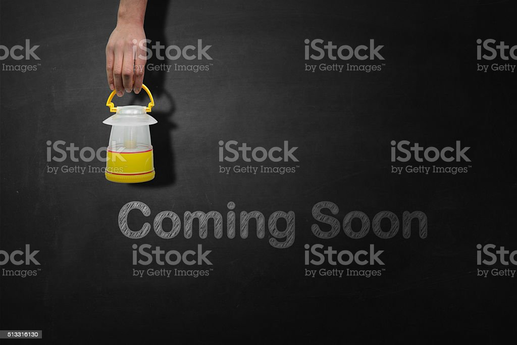 Coming soon message on blackboard stock photo