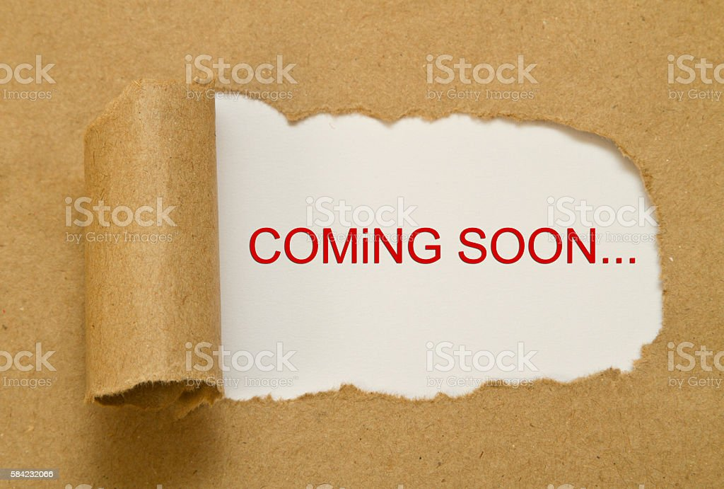 coming soon message written under torn paper stock photo
