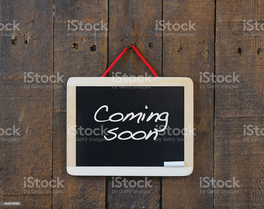 Coming soon sign nailed to a wooden wall stock photo