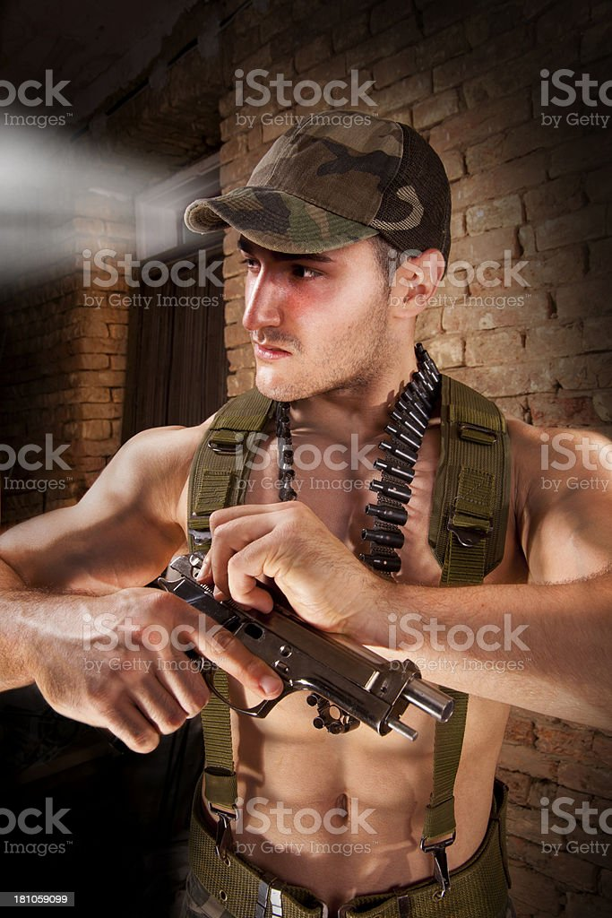 Commando aiming with a pistol against  brick background royalty-free stock photo