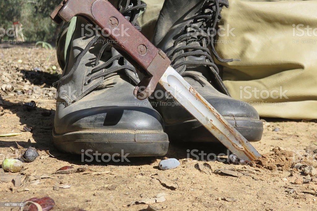 commando knife alongside army boots stock photo