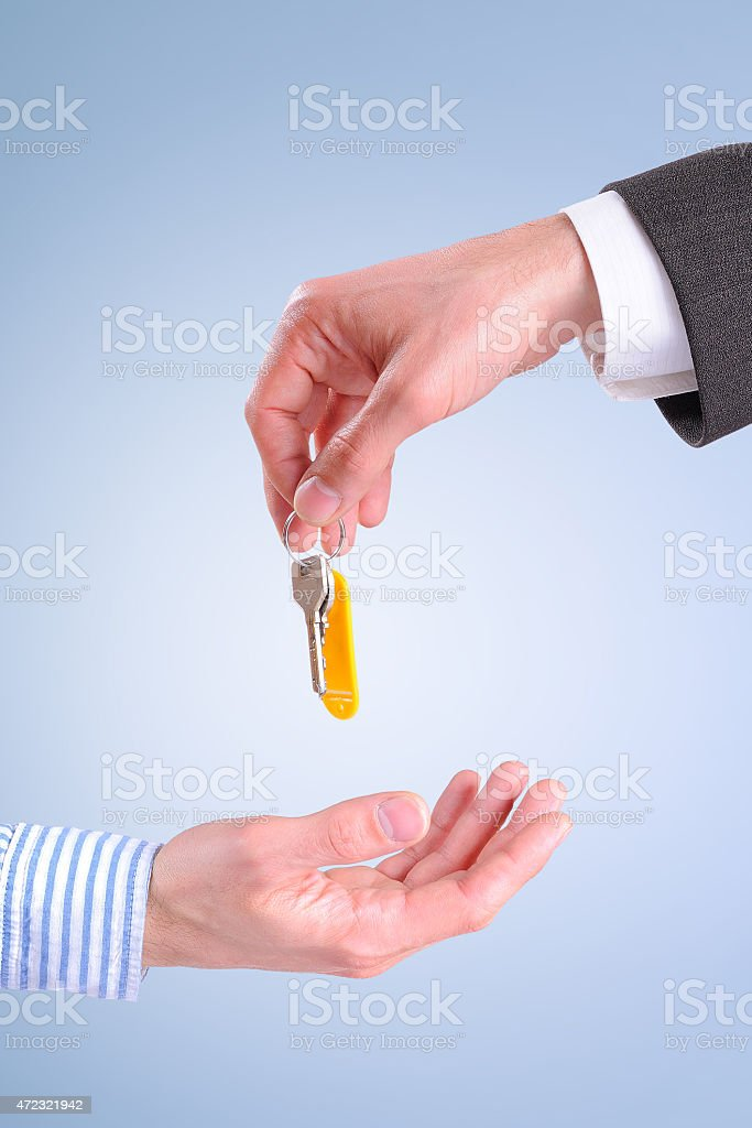 Commercial agent giving keys to customer isolated vertical compo stock photo
