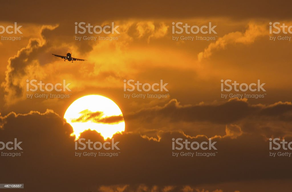 Commercial Aircraft On Approach Above Large Summer Sunrise royalty-free stock photo