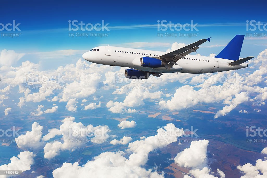 Commercial airliner flying above clouds with blue sky in background. stock photo