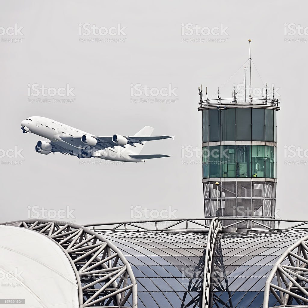 Commercial airliner passes an airport control tower at take-off. stock photo