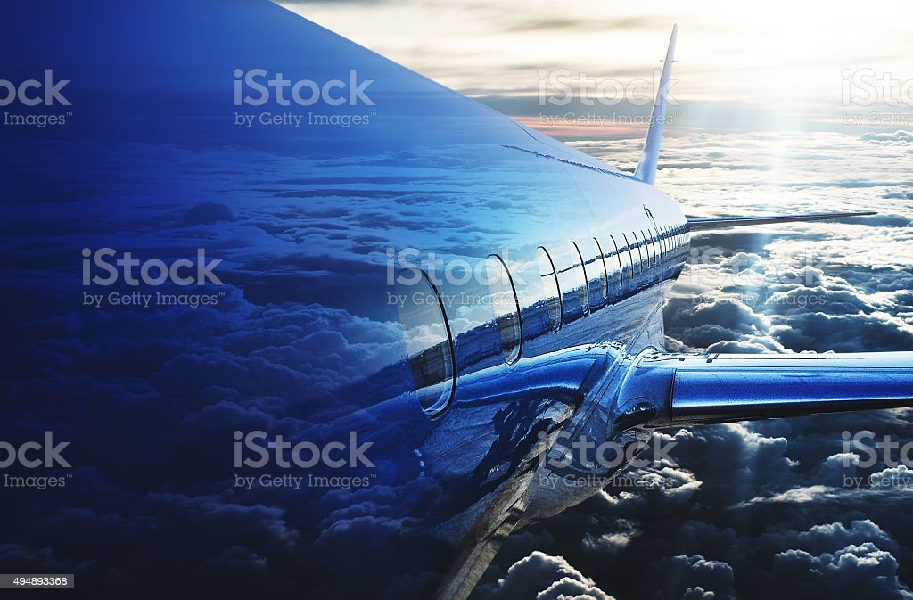 commercial airplane flying on the clouds stock photo