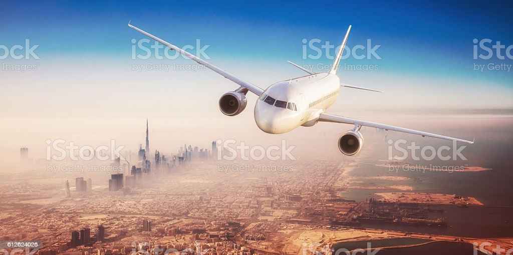 Commercial airplane flying over modern city stock photo