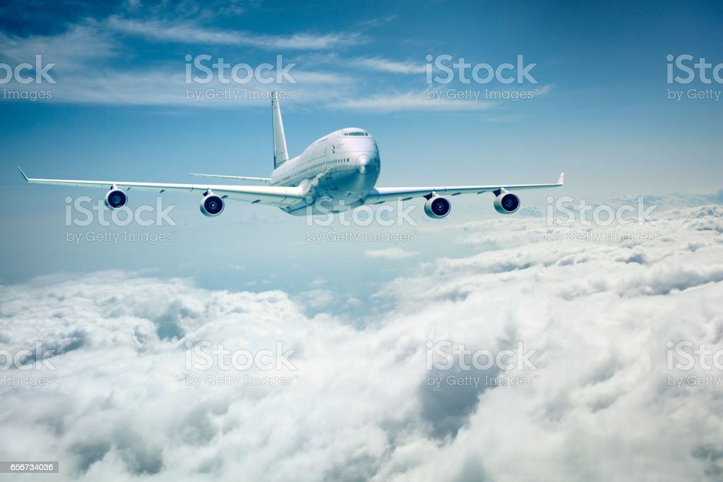 commercial airplane flying over the clouds stock photo
