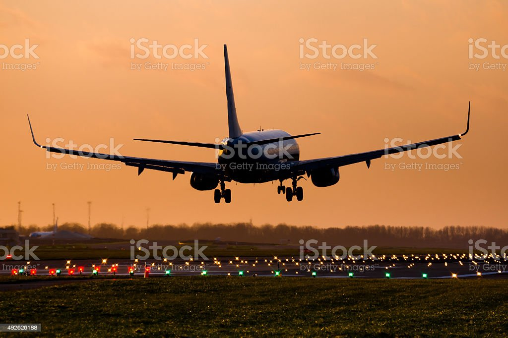 A commercial aircraft landing during the golden hour.