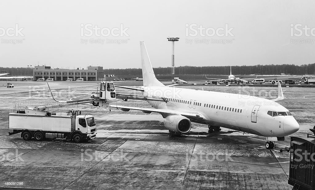 Commercial airplane parked and serviced at the airport stock photo