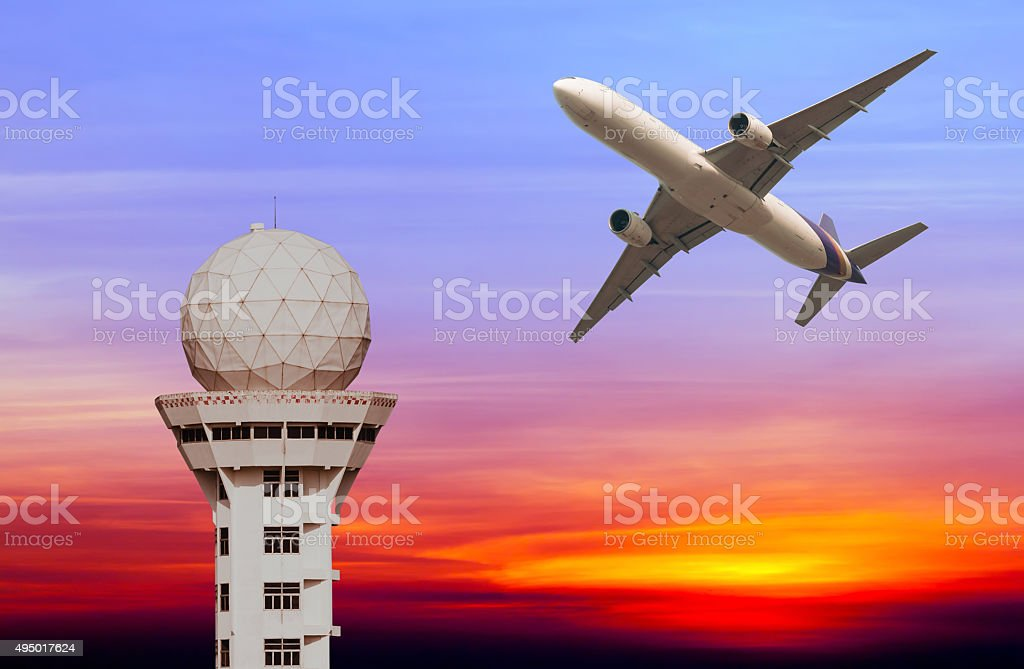 Commercial airplane take off over airport control tower at sunse stock photo