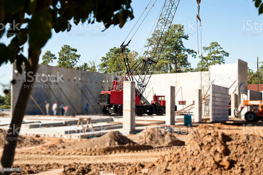 Commercial crane vehicle places walls at new construction business site. stock photo
