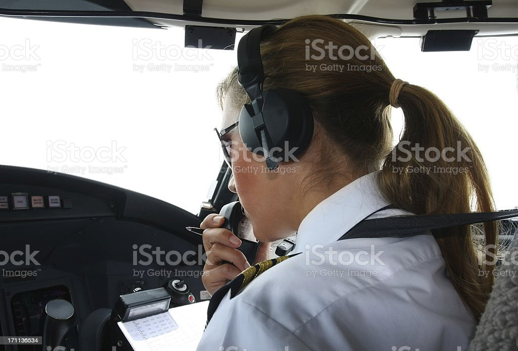 Commercial jet flyin...beautiful woman pilot checking data royalty-free stock photo