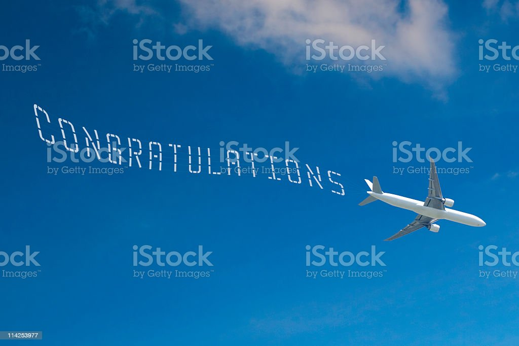 Commercial jet pulls CONGRATULATIONS banner stock photo